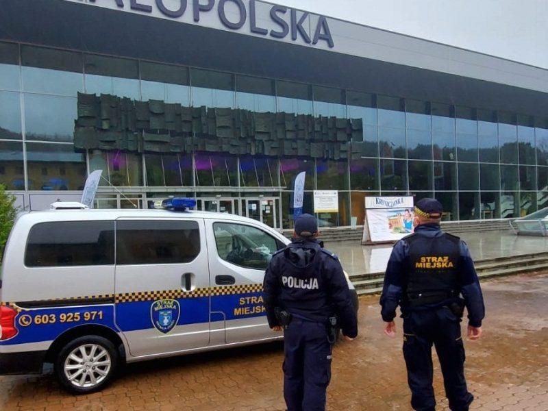 Policjant i strażnik miejski na tle radiowozu w Krynicy-Zdroju
